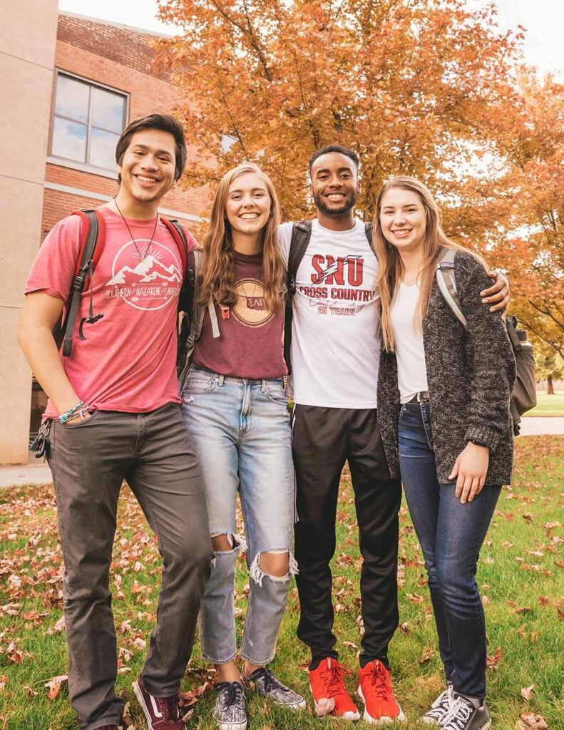 Four students standing on Campus smiling