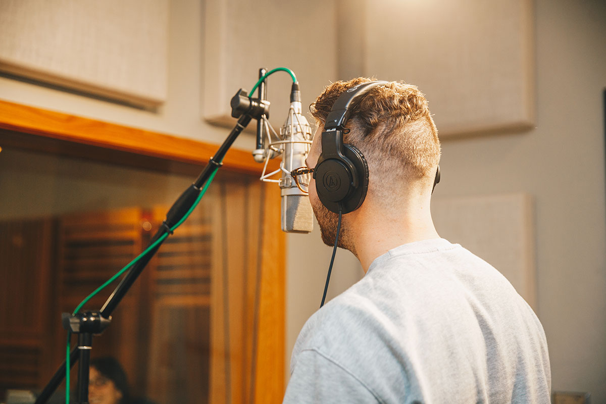 Student sings in recording studio