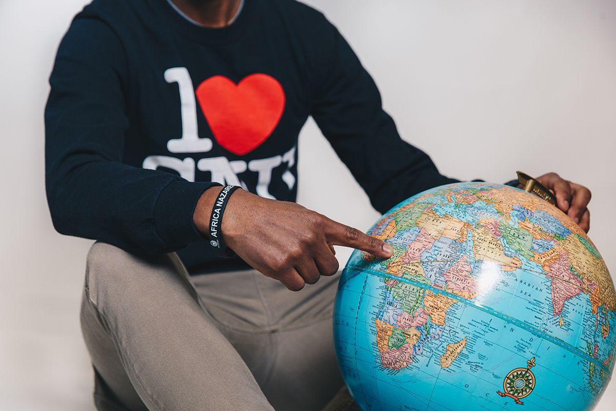 student pointing to globe
