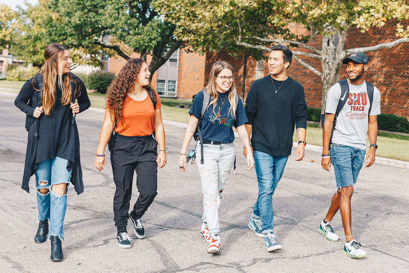 Group of students walking across campus in the fall