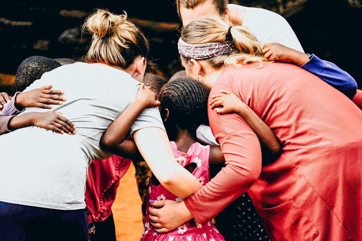 Students hug children on mission trip