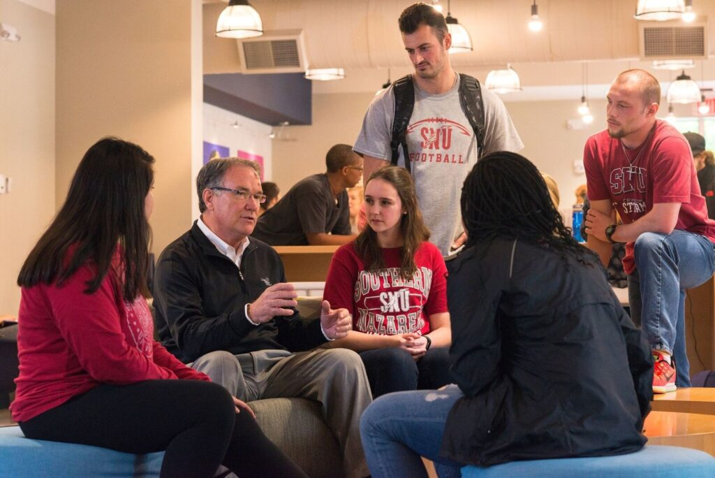 group of students talking to professor
