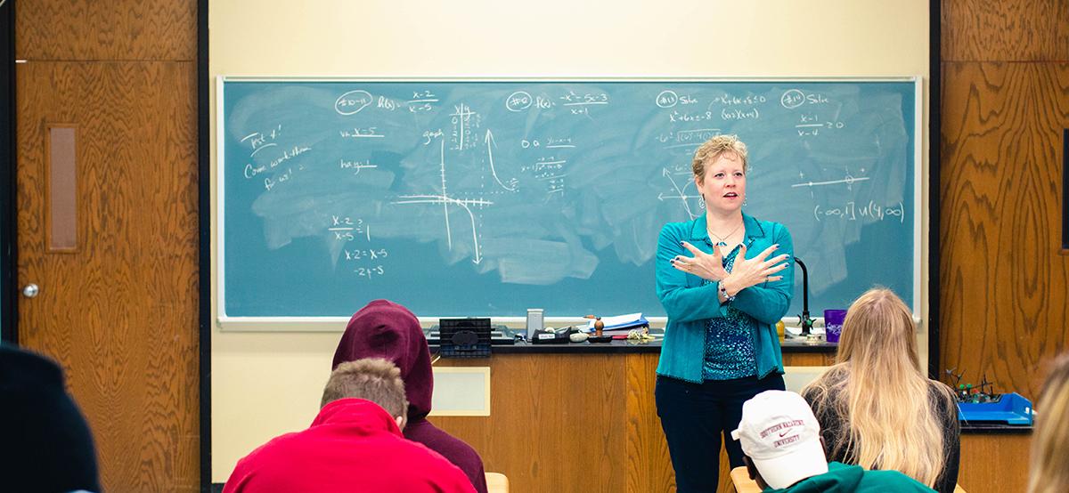 professor teach math in front of a chalk board