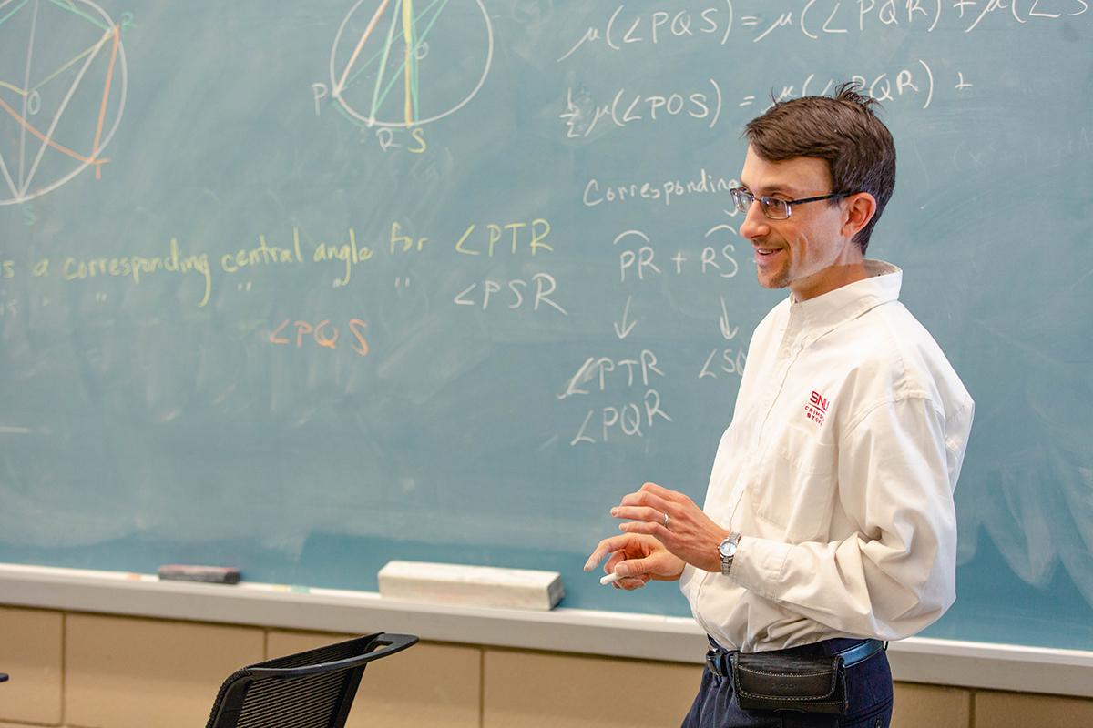 professor at the chalkboard teaching math