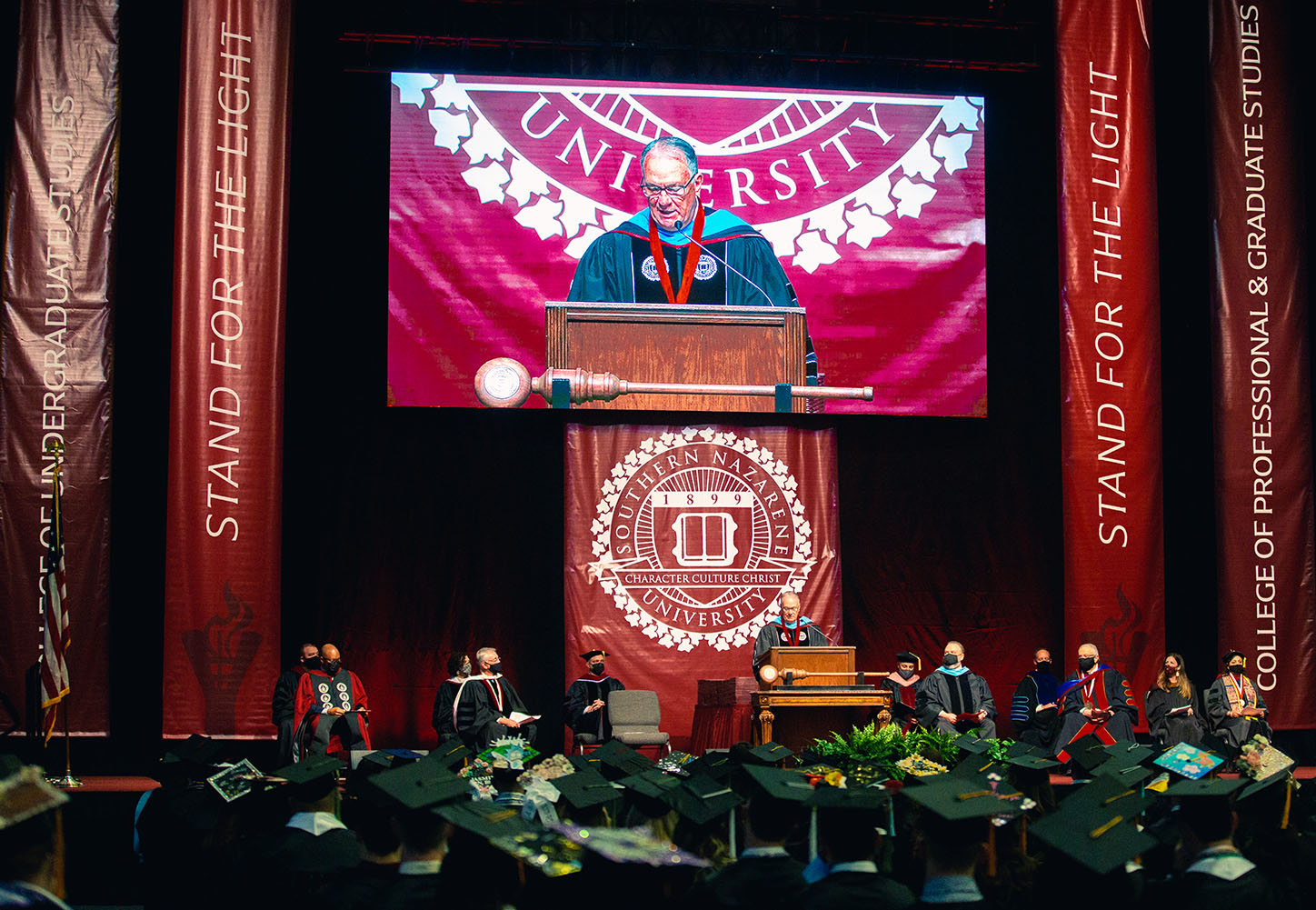 Wide image of stage from Commencement with speaker at podium